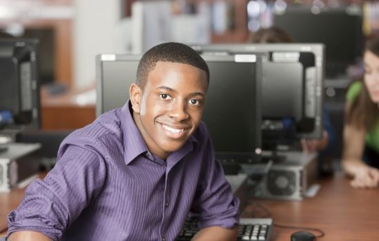 Young adult male student smiling in front of a desktop computer
